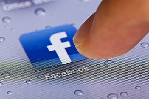 A finger tapping the Facebook app on a phone