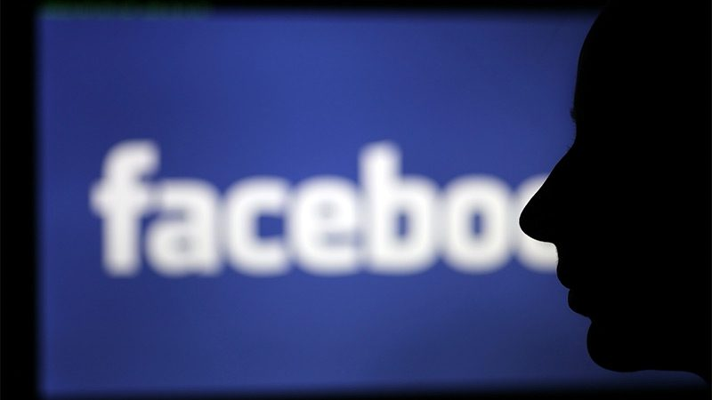 The Facebook logo behind the silhouette of a face